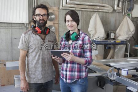 portrait of confident carpenters with digital