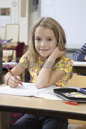 girl with book in classroom portrait