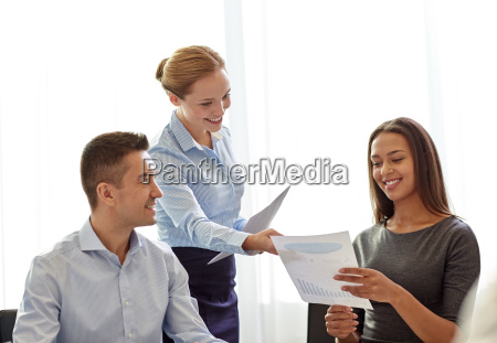 smiling business people with papers in