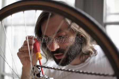 mid adult man repairing bicycle at