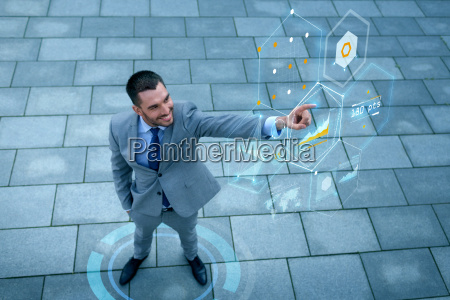 smiling businessman with virtual screens outdoors