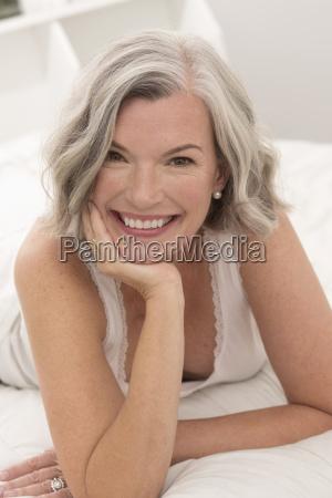 portrait of happy mature woman lying