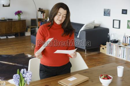 mature woman holding letters while standing