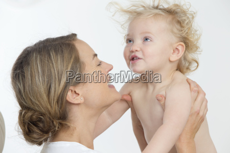 smiling mother holding happy baby with
