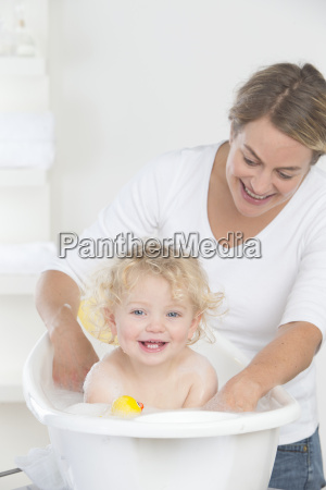 smiling mother bathing happy baby in