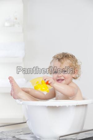 smiling baby sitting in bathtub holding