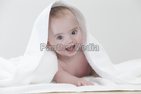 smiling baby laying on towel