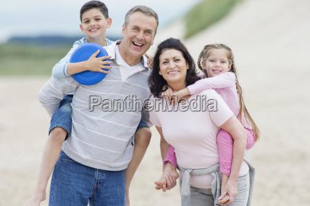 grandparents carrying grandchildren piggyback on beach