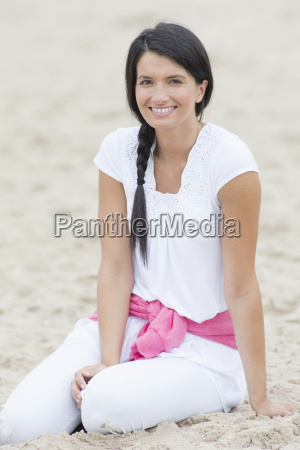 smiling woman sitting in sand on