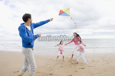 family flying kite on beach