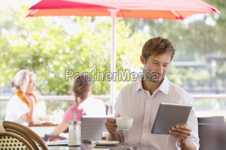 man drinking coffee with digital tablet