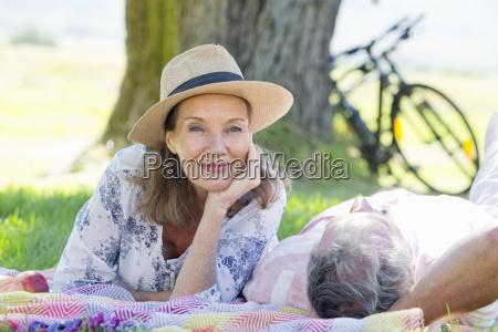senior couple lying on picnic blanket
