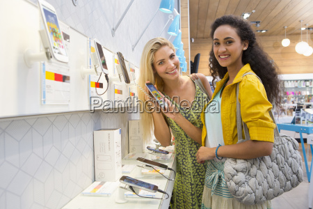 young female friends shopping in phone