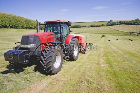 tractor baling hay in field