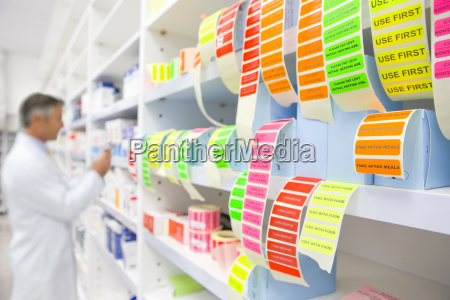 labels in foreground and pharmacist looking