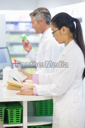pharmacists counting medication behind pharmacy counter
