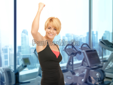 happy woman fitness instructor over gym