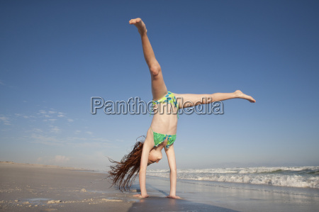 redheaded girl doing handstand on sunny
