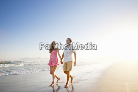 smiling couple holding hands walking along