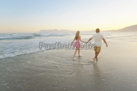 couple holding hands walking through waves