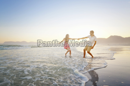 couple holding hands playfully walking through
