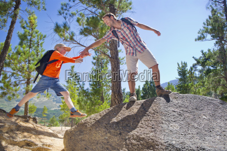 father helping son climb on mountain