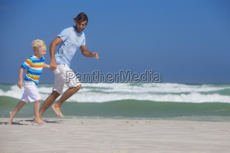 father and son holding hands running