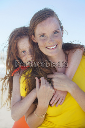 portrait of smiling girl embracing mother