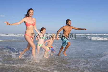happy family in swimwear running through