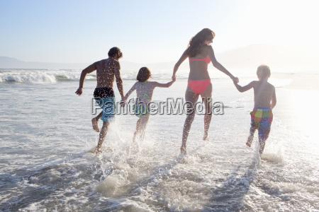 happy family in swimwear running through
