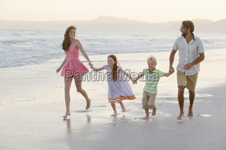 happy family holding hands running along