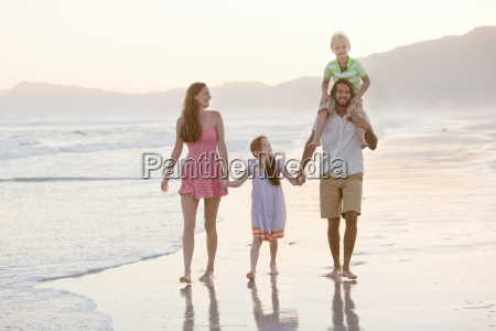 happy family walking through waves holding