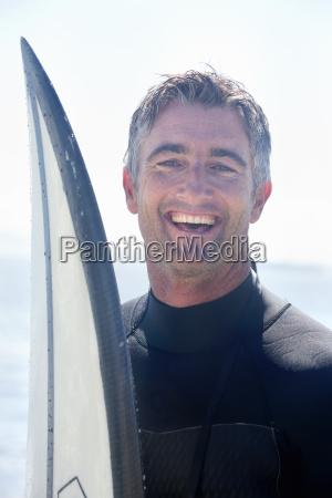 portrait of surfer with surfboard smiling
