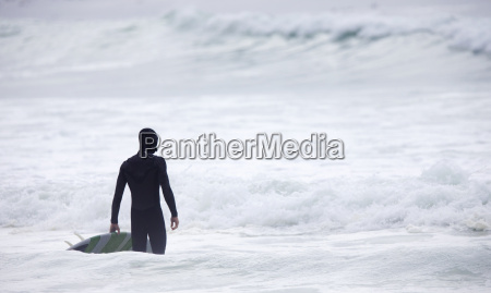 man holding surfboard looking out to