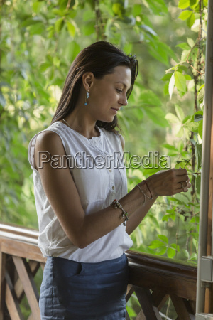 young woman touching plant while standing