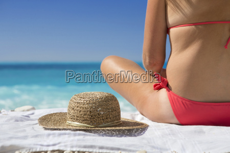 woman sitting on towel with sun