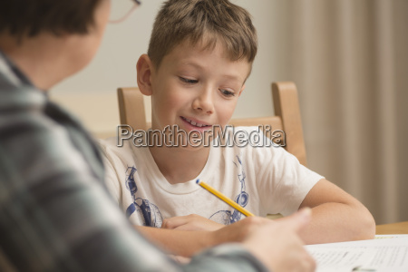 grandmother teaching boy on table at