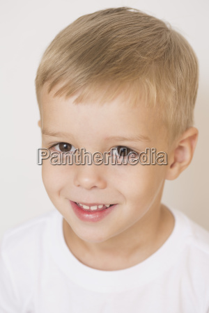 portrait of smiling boy against white