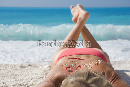 woman sunbathing with sand on back