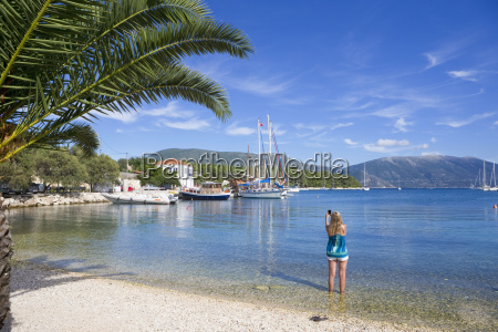 woman taking photo of boats on