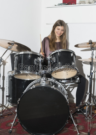 happy young woman playing drums