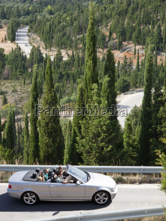 family driving convertible car along tree