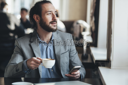 mid adult businessman holding coffee cup