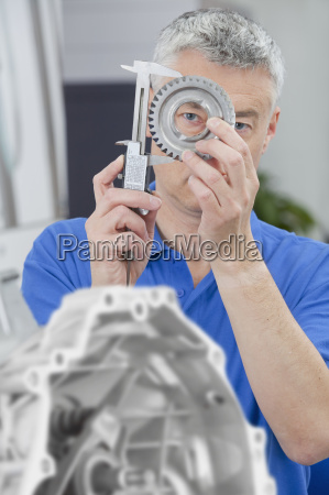 engineer measuring gear wheel with vernier