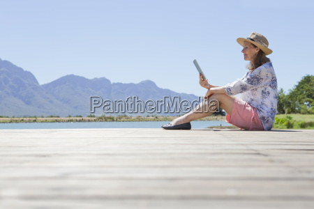senior woman sitting on jetty with