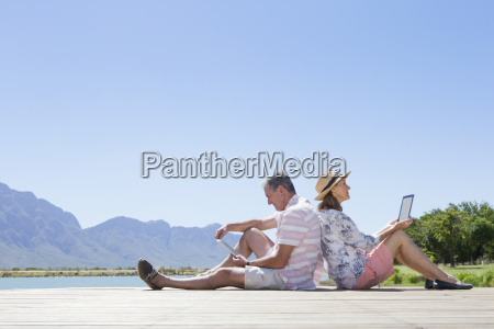 senior couple sitting on wooden jetty