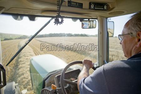 farmer at steering wheel of tractor