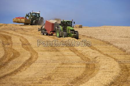tractors baling straw and stacking bales