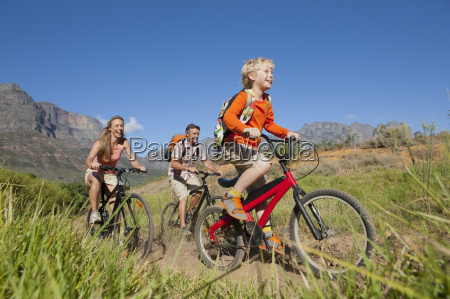 family mountain biking on country track