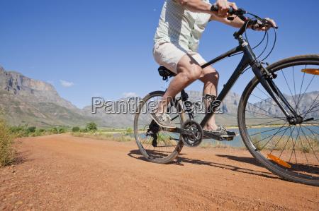 senior man mountain biking on country